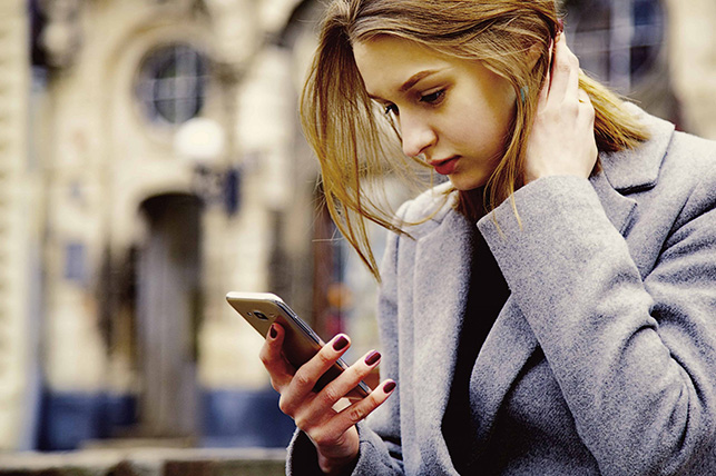 Angry and sad young woman looking at cell phone seeing bad text message, email.