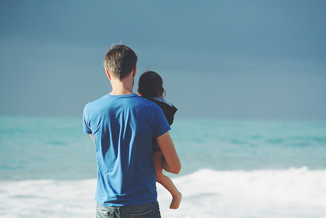 Dad holding daughter looking at ocean waves